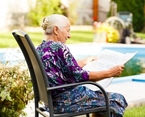 Elderly lady reading newspaper peacefully in her beautiful garden.
